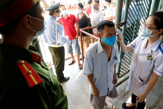 PHOTO DE DOSSIER: Un agent de santé vérifie la température d'un fan de football avant un match de football entre Viettel et Duoc Nam Ha Nam Dinh de la V.League, la ligue nationale de football, après que le gouvernement a assoupli le verrouillage à l'échelle nationale à la suite de la maladie du coronavirus (COVID-19 ) épidémie dans la province de Nam Dinh, Vietnam, 5 juin 2020. REUTERS / Kham / File Photo