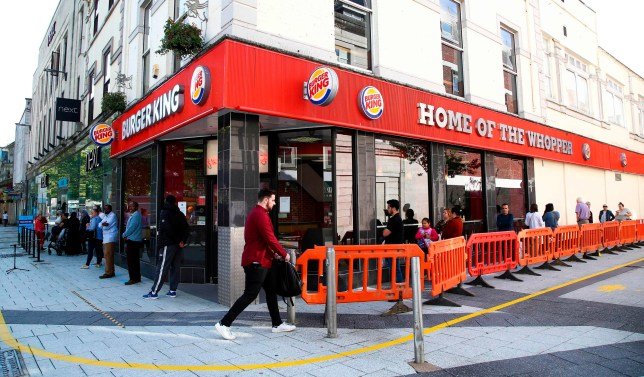 Shoppers maintain the British government's current social distancing guidelines and stand two metres (2M) apart as they queue to enter a Burger King fast Food store (R) and Next Store (L) in Cardiff on June 22, 2020, as some non-essential retailers in Wales are able to reopen from their enforced coronavirus shutdown. - Various stores and outdoor attractions in Wales are set to open Monday for the first time in nearly three months, as the government continues to ease its coronavirus lockdown, but pubs and restaurants must remain closed, and people must still stay 'local', where possible. (Photo by GEOFF CADDICK / AFP) (Photo by GEOFF CADDICK/AFP via Getty Images)