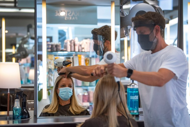 Senior Style Director Nick Peters wears PPE as he cuts a staff member's hair at Daniel Galvin hairdressers