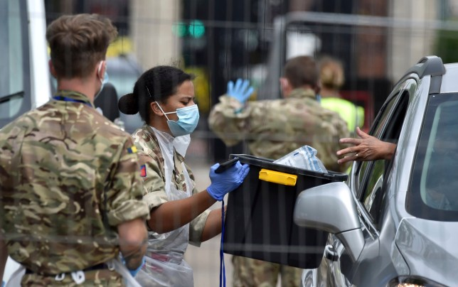 Members of the army work at a coronavirus testing station set up in Victoria Park in Leicester, England