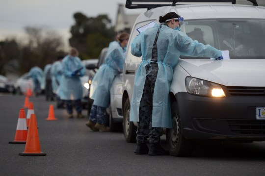 Members of the Australian Defence Force (ADF) gather information and conduct temperature checks at a drive-in Covid-19 testing site set up at the Melbourne Show Grounds in Melbourne, Victoria, Australia, on Tuesday, Jun 30, 2020. Victoria, Australia's second-most populous state, faces isolation from much of the country due to a spike in coronavirus cases that's jeopardizing the economic recovery. Photographer: Carla Gottgens/Bloomberg via Getty Images - 8474891
