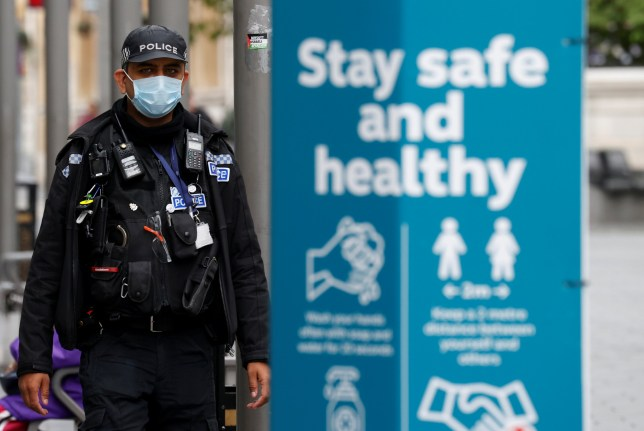 A police officer wearing a protective mask is pictured as he patrols along a street