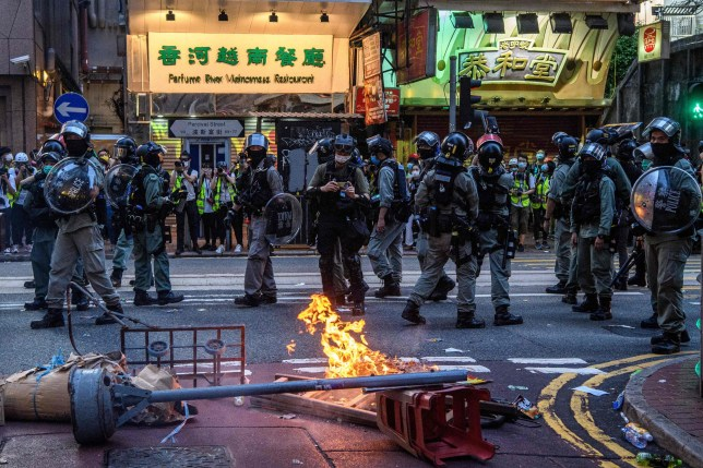 Police walk past a burning barricade set up by protesters during a rally against a new national security law in Hong Kong on July 1, 2020, on the 23rd anniversary of the city's handover from Britain to China. - Hong Kong police arrested more than 300 people on July 1 -- including nine under China's new national security law -- as thousands defied a ban on protests on the anniversary of the city's handover to China. (Photo by Anthony WALLACE / AFP) (Photo by ANTHONY WALLACE/AFP via Getty Images)