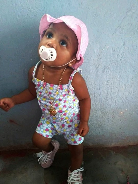 In this Feb. 10, 2020, photo, provided by Andr??a de Sousa, her daughter Vitoria Gabrielle looks up while leaning against a wall, in Rio de Janeiro, Brazil. The girl with a constant smile celebrated her first birthday in February, but after recovering from viral meningitis, Vitoria Gabrielle suffered gastrointestinal problems that sent her from her mother's barely furnished hilltop home back to the hospital several times for treatment. It was during an April hospital stay that de Sousa suspects her daughter was infected with the coronavirus that was just starting to circulate in Rio and Brazil. Vitoria Gabrielle died in June. (Courtesy of Andr??a de Sousa via AP)