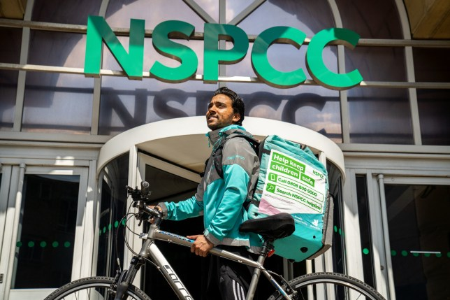 Deliveroo rider Abdelziz Abdou sits on his bike with an NSPCC sign on his bag outside an NSPCC building.