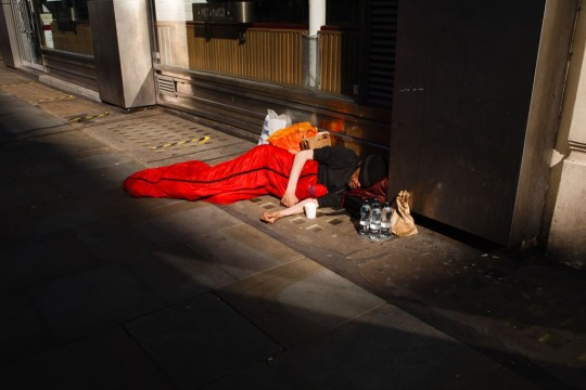 A homeless man sleeps on Cranbourn Street in London, England,