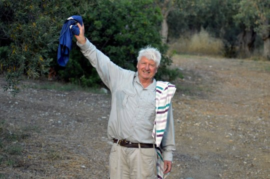 Stanley Johnson, father of British Prime Minister Boris Johnson, greets local journalists outside his villa Irene in the village of Horto, Mount Pelion (also known as Pilio), in central Greece, Friday July 3, 2020. Johnson is arrived in Athens Wednesday evening after flying via Bulgaria due to a current ban on direct flights from Britain, before visiting his villa on Mount Pelion. (Dimitris Kareklidis / magnesianews.gr via AP)