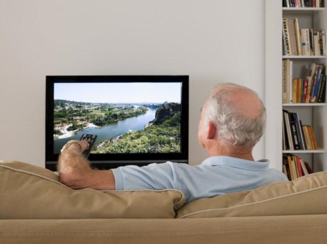 An elderly man watching TV