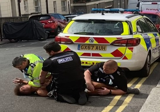NOTE: FACE OF RESTRAINED MAN PIXELATED BY THE PA PICTURE DESK TO PROTECT HIS IDENTITY Undated handout photo of a man lying on the ground, restrained by three officers, behind a police car in Brighton. Sussex Police is reviewing whether footage of its officers restraining a man who repeatedly shouts ?I can?t breathe? needs to be investigated. PA Photo. Issue date: Thursday July 9, 2020. In a video circulating on social media, a man is lying on the ground, restrained by three officers, on a hill behind a police car in Brighton. Sussex Police said the man was arrested and became aggressive towards officers before being placed on the ground. The incident has been also referred to the Independent Office for Police Conduct (IOPC). See PA story POLICE Montpelier. Photo credit should read: PA/PA Wire NOTE TO EDITORS: This handout photo may only be used in for editorial reporting purposes for the contemporaneous illustration of events, things or the people in the image or facts mentioned in the caption. Reuse of the picture may require further permission from the copyright holder.