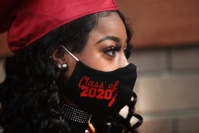 BRADLEY, ILLINOIS - MAY 06: Makeya Butler waits to have her picture taken before receiving her diploma at a graduation ceremony at Bradley-Bourbonnais Community High School on May 06, 2020 in Bradley, Illinois. Because of social distancing mandates instituted by the state to curtail the spread of COVID-19, graduates received their diplomas in a nearly-empty auditorium with no friends, family or relatives allowed to attend. A video of the event will be streamed for others to view on the the school's scheduled graduation date of May 16. The school, located about 60 miles south of Chicago, has about 2,100 students, 523 were graduating. (Photo by Scott Olson/Getty Images)
