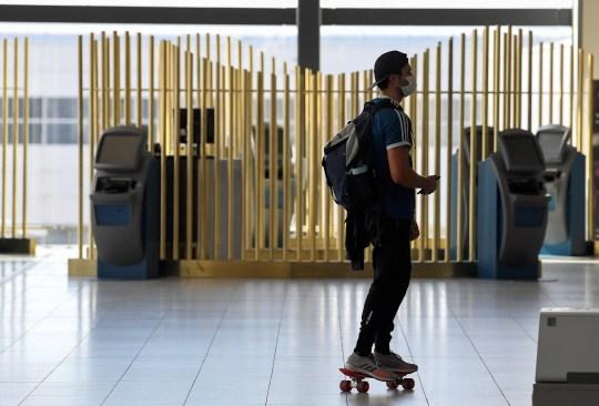 Un passager utilise une planche à roulettes dans un terminal de départ à l'aéroport de Gatwick, car les restrictions de voyage sont assouplies à la suite de l'épidémie de maladie à coronavirus (COVID-19), à Gatwick, en Grande-Bretagne, le 10 juillet 2020. REUTERS / Toby Melville