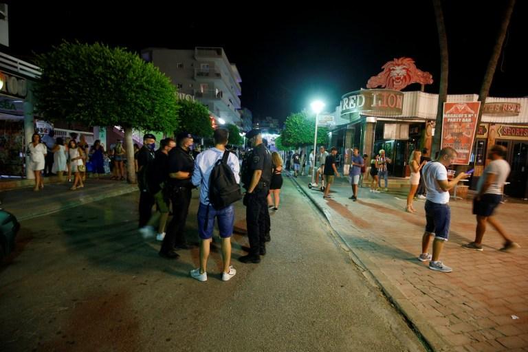 Des agents de police portant des masques de protection patrouillent dans la rue plus calme de Punta Ballena à Magaluf alors que les bars sont fermés, au milieu de l'épidémie de la maladie à coronavirus (COVID-19), à Majorque, Espagne, le 12 juillet 2020. REUTERS / Enrique Calvo