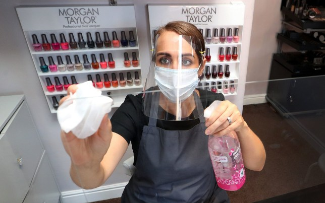 PABest Roberta Dyer, owner of Roberta Beauty Redefined in Knutsford, Cheshire, wears PPE while she cleans a protective screen as they prepare to reopen following the further easing of coronavirus lockdown measures in England. PA Photo. Picture date: Sunday July 12, 2020. Nail bars will be allowed to reopen on Monday July 13, along with beauty salons, tattoo and massage studios, physical therapy businesses, spas and piercing services. See PA story HEALTH Coronavirus. Photo credit should read: Martin Rickett/PA Wire