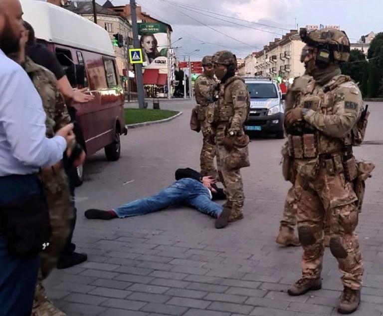Un assaillant, qui a saisi un bus longue distance avec 10 otages, gît au sol après que des policiers l'ont capturé dans le centre-ville de Loutsk, à quelque 400 kilomètres (250 miles) à l'ouest de Kiev, en Ukraine, le mardi 21 juillet 2020. l'assaillant était armé et transportait des explosifs, selon une déclaration sur Facebook de la police ukrainienne.  (Bureau de presse de la police ukrainienne via AP)