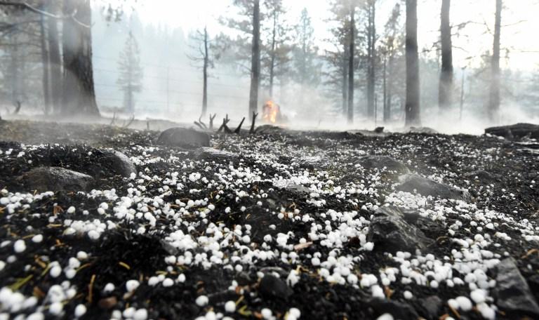 Une souche d'arbre continue de brûler alors que la grêle recouvre le sol lorsqu'elle est tombée directement sur l'incendie de Hog près de Susanville, en Californie, le 21 juillet 2020. - Une cellule d'orage mélangée à une colonne de cendres de pyrocumulus du feu de Hog, entraînant des vents erratiques et des éclairs avant d'évoluer vers une tempête de grêle qui a éteint une partie de l'incendie.