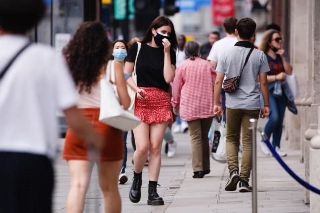 A woman wearing a face mask walks amid shoppers on Regent Street in London, England