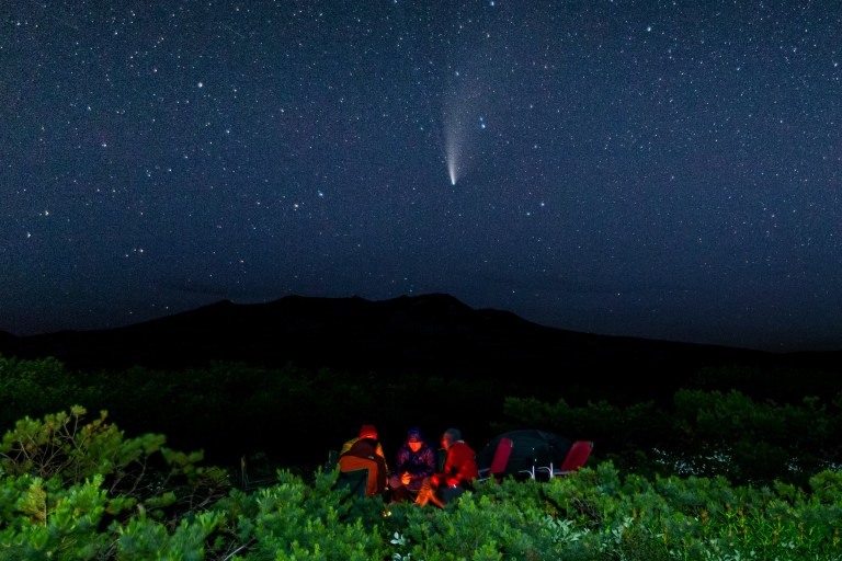 TERRITOIRE DU KAMCHATKA, RUSSIE - 21 JUILLET 2020: Des touristes s'assoient autour d'un feu dans un camping au pied du mont Mutnovsky dans le parc naturel régional du sud du Kamtchatka, sur la côte pacifique de la Russie. Le parc régional du sud du Kamtchatka fait partie d'un groupe de parcs naturels connus sous le nom de parc des volcans du Kamtchatka, qui est sur la liste du patrimoine mondial de l'UNESCO depuis 1996. Vue dans le ciel, la comète NEOWISE (C / 2020 F3). La comète NEOWISE a été découverte le 27 mars 2020, lors de la mission NEOWISE du télescope spatial Wide-field Infrared Survey Explorer (WISE). Yelena Vereshchaka / TASS (Photo par Yelena Vereshchaka \ TASS via Getty Images)