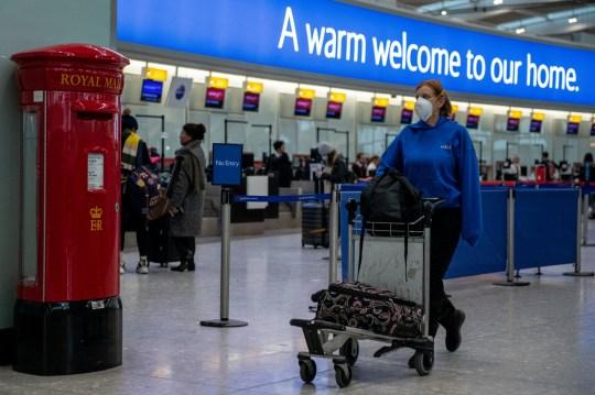 Londres, ANGLETERRE - 15 MARS: Un passager de la compagnie aérienne portant un masque facial pousse ses sacs devant une boîte aux lettres aux départs du terminal 5 d'Heathrow alors que l'épidémie de coronavirus s'intensifie le 15 mars 2020 à Londres, en Angleterre.  Le président des États-Unis, Donald Trump, a mis en place une interdiction de voyager dans les pays européens et l'a maintenant étendue au Royaume-Uni et à l'Irlande.  L'interdiction de voyager commencera lundi à minuit, heure de l'Est, alors que le Royaume-Uni est également sur le point d'interdire les rassemblements de masse et a déjà vu l'annulation de grands événements sportifs tels que la Premier League anglaise.  (Photo par Chris J Ratcliffe / Getty Images)