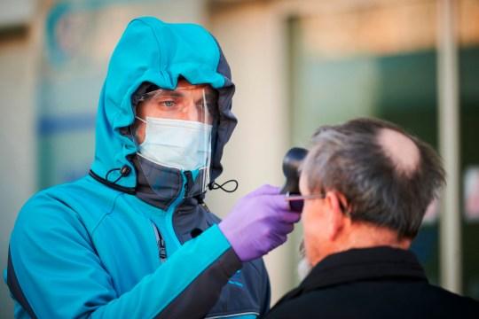 TOPSHOT - Un travailleur médical mesure la température corporelle à l'une des entrées du centre de santé communautaire de Kranj, en Slovénie, le 23 mars 2020 au milieu des inquiétudes concernant la propagation du coronavirus COVID-19.  (Photo par Jure Makovec / AFP) (Photo par JURE MAKOVEC / AFP via Getty Images)
