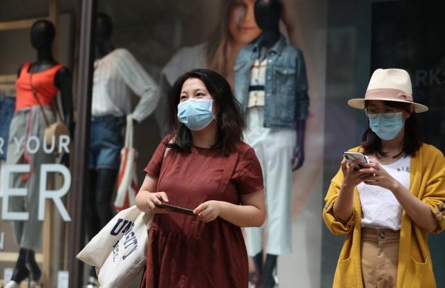 People wear masks as they walk along Broadmead in Bristol