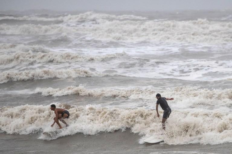 Les résidents locaux Alejandero Carcano, 16 ans, et Jesse Garewal, 18 ans, surfent dans les fortes houles de l'ouragan Hanna à Galveston, Texas, États-Unis, le 25 juillet 2020. REUTERS / Adrees Latif.