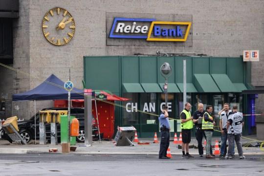 Des responsables discutent près d'une voiture qui s'est écrasée sur un groupe de sept personnes à la gare Bahnhof Zoo de Berlin, Allemagne, le 26 juillet 2020.