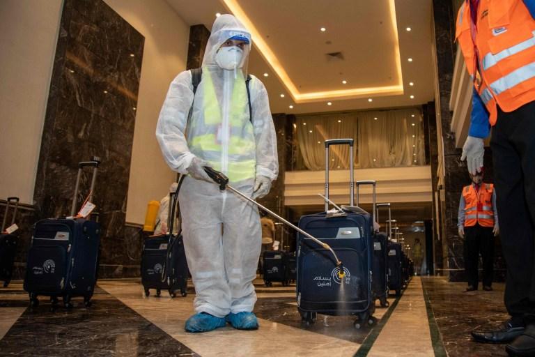 Les travailleurs désinfectent les bagages des pèlerins dans le hall d'un hôtel situé près de la Grande Mosquée de la ville sainte de La Mecque en Arabie saoudite