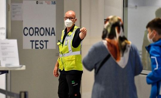Un garde indique aux passagers à l'arrivée un test COVID-19 dans un nouveau centre de test de l'aéroport de Düsseldorf, en Allemagne, le lundi 27 juillet 2020. De nouveaux centres de test pour le coronavirus sont établis dans les aéroports allemands en raison de la pandémie, des tests corona gratuits sont accordés aux rapatriés des pays désignés comme zones à risque.  (Photo AP / Martin Meissner)
