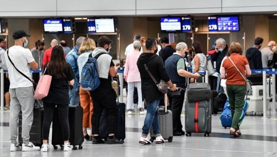 Les voyageurs s'enregistrent pour les vols à l'aéroport de Düsseldorf, en Allemagne, le lundi 27 juillet 2020. De nouveaux centres de test du coronavirus sont établis dans les aéroports allemands en raison de la pandémie, des tests corona gratuits sont donnés aux rapatriés des pays désignés comme zones à risque.  (Photo AP / Martin Meissner)