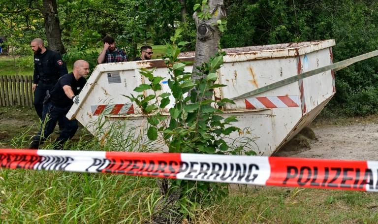Des agents de police allemands retirent un conteneur lors d'une perquisition dans une parcelle de jardin à Seelze, près de Hanovre, en Allemagne, le mercredi 29 juillet 2020. La police a commencé à fouiller une parcelle de jardin, supposée être liée à la disparition des disparus au Portugal en 2007 Fille britannique Madeleine McCann.  (Photo AP / Martin Meissner)