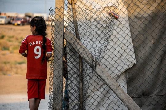 Une jeune fille se tient à côté d'un abri portant l'uniforme de football de l'attaquant français de Manchester United Anthony Martial dans un camp pour personnes déplacées à l'intérieur du pays (PDI) de la minorité yézidie irakienne dans la région de Sharya
