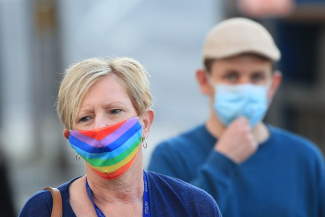 A woman wearing a face mask walks through the centre of Bradford,