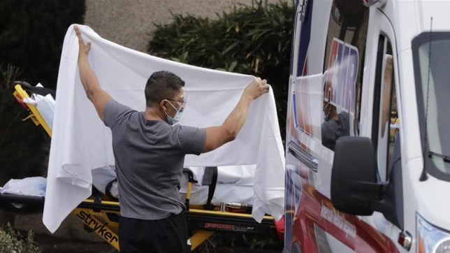 Man placing sheet over coronavirus patient