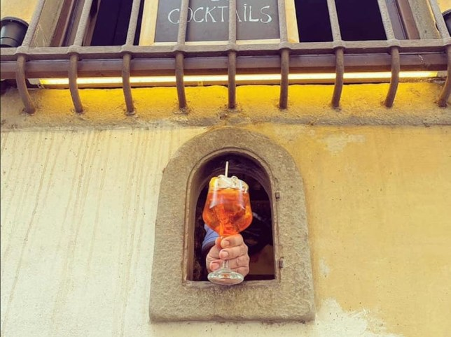wine window in tuscany handing out aperol spritz