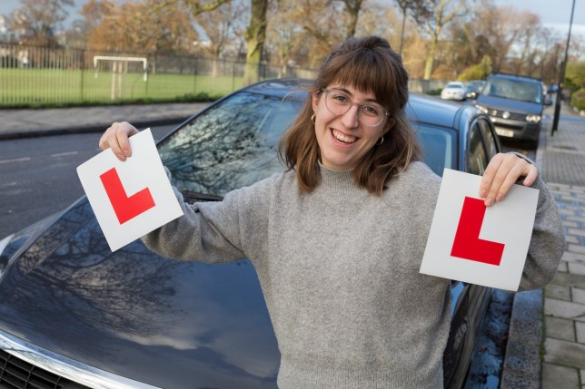 A young 23 year-old woman celebrates the passing of her driving test by holding up her L Plates in front of the family car.