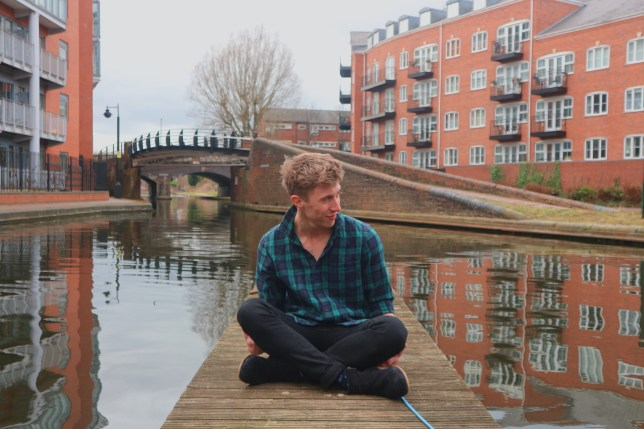 James Hawks sitting on a wooden plank on the river
