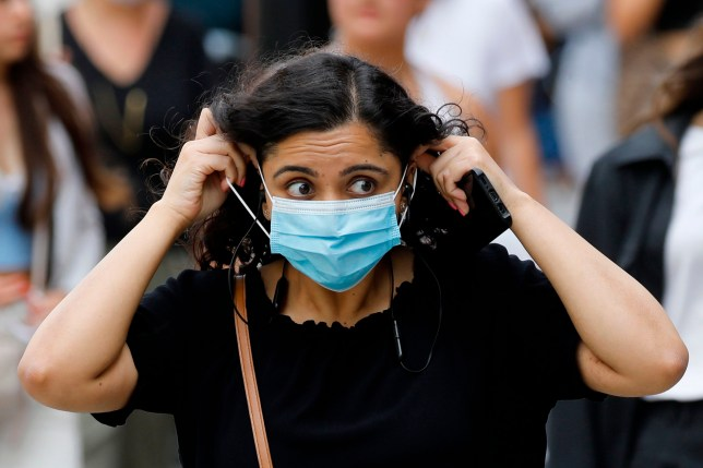 A shopper adjusts her face mask on Oxford Street in London