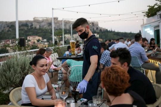 1 Αυγούστου 2020 Στην Αθήνα, Ελλάδα, εν μέσω της εξάπλωσης της νόσου της κορώνας (COVID-19), ένας υπάλληλος φορά μάσκα ασφαλείας ενώ εργαζόταν σε μπαρ.