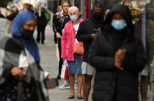 People, some wearing face masks or covering due to the COVID-19 pandemic, queue to enter a shop in Manchester