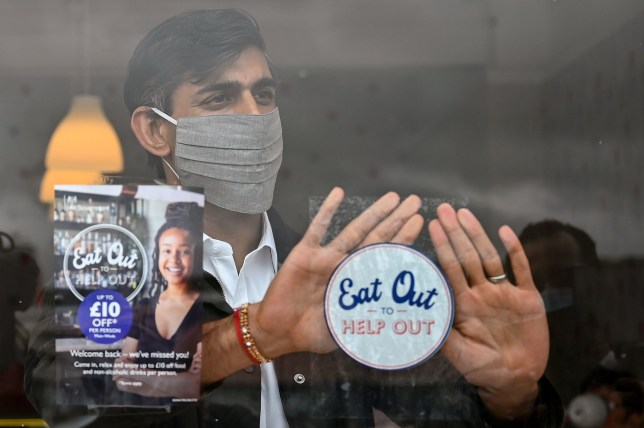 Chancellor of the Exchequer Rishi Sunak places an Eat Out to Help Out sticker in the window of a business