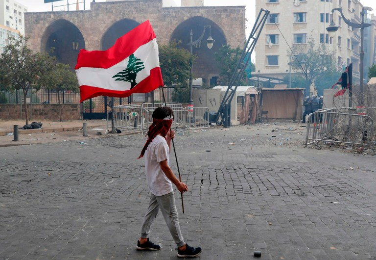 A Lebanese protester waves the national flag during clashes in downtown Beirut on August 8, 2020, following a demonstration against a political leadership they blame for a monster explosion that killed more than 150 people and disfigured the capital Beirut. (Photo by ANWAR AMRO / AFP) (Photo by ANWAR AMRO/AFP via Getty Images)