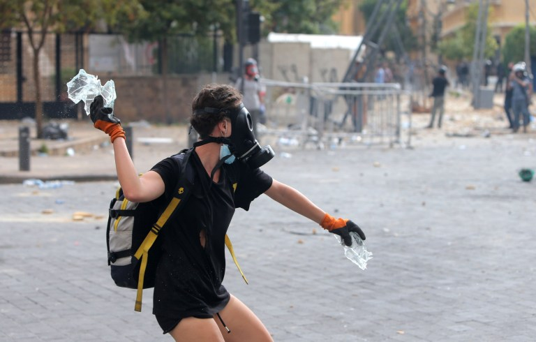 A Lebanese protester hurls glass towards security forces during clashes in downtown Beirut on August 8, 2020, following a demonstration against a political leadership they blame for a monster explosion that killed more than 150 people and disfigured the capital Beirut. (Photo by STR / AFP) (Photo by STR/AFP via Getty Images)