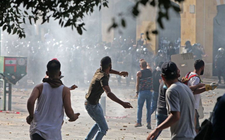 TOPSHOT - Lebanese protesters hurl rocks towards security forces during clashes in downtown Beirut on August 8, 2020, following a demonstration against a political leadership they blame for a monster explosion that killed more than 150 people and disfigured the capital Beirut. (Photo by STR / AFP) (Photo by STR/AFP via Getty Images)