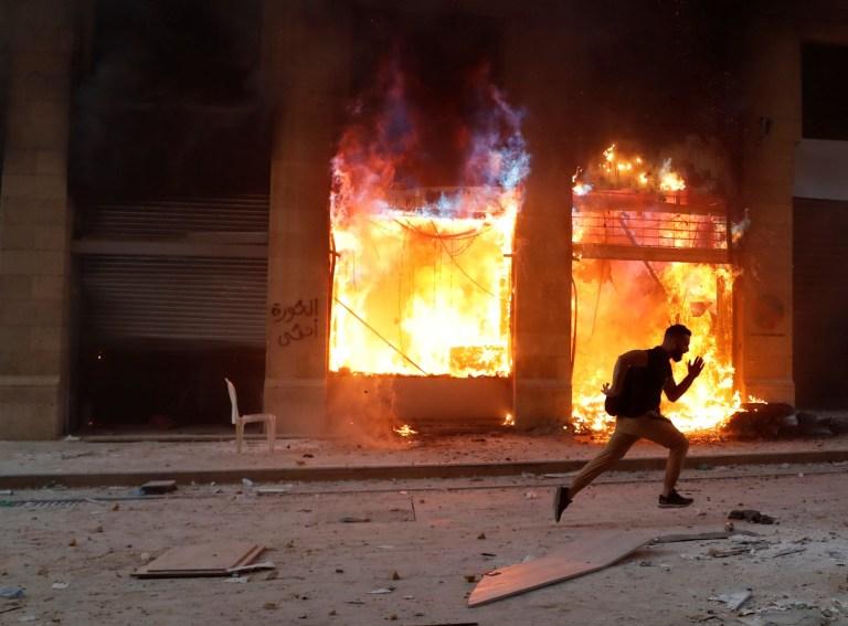 Un manifestant s'enfuit des forces de sécurité, devant un bâtiment en feu lors d'une manifestation à Beyrouth, Liban, le 8 août 2020. REUTERS / Goran Tomasevic