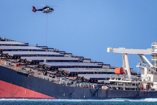 A helicopter hovers over the vessel MV Wakashio, belonging to a Japanese company but Panamanian-flagged, that ran aground and caused oil leakage near Blue bay Marine Park in southeast Mauritius on August 8, 2020. - France on August 8, 2020 dispatched aircraft and technical advisers from Reunion to Mauritius after the prime minister appealed for urgent assistance to contain a worsening oil spill polluting the island nation's famed reefs, lagoons and oceans. Rough seas have hampered efforts to stop fuel leaking from the bulk carrier MV Wakashio, which ran aground two weeks ago, and is staining pristine waters in an ecologically protected marine area off the south-east coast. (Photo by Daren Mauree / L'Express Maurice / AFP) (Photo by DAREN MAUREE/L'Express Maurice/AFP via Getty Images)