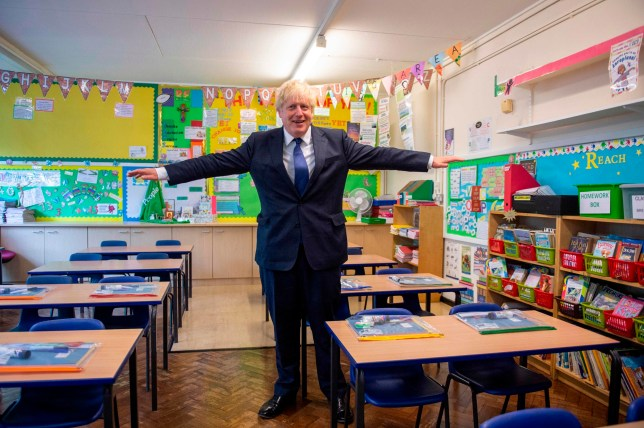 Britain's Prime Minister Boris Johnson poses with his arms out-stretched in a classroom as he visits St Joseph's Catholic Primary School in Upminster, east London