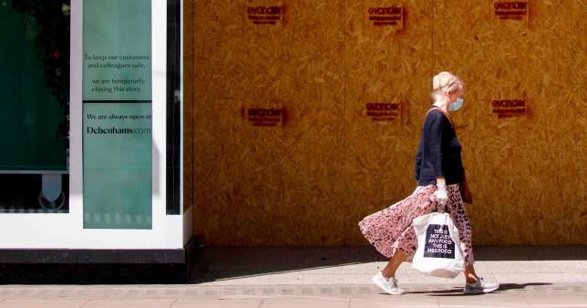 a woman walks past an empty debenhams store