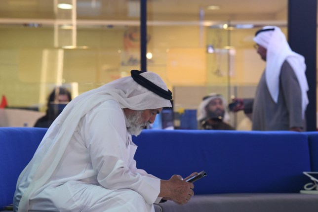 A trader checks his smart phone at the Dubai Financial Market in the Gulf emirate on January 6, 2020, as Gulf bourses were hit by a panicky sell-off amid Iranian vows of retaliation over the US killing of a top general. - All seven bourses in the Gulf Cooperation Council (GCC) states closed in the red, on the first trading day since the death of powerful military commander Qasem Soleimani. (Photo by Karim SAHIB / AFP) (Photo by KARIM SAHIB/AFP via Getty Images)