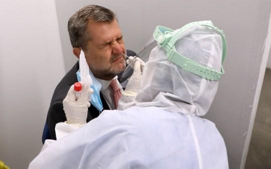 epa08615912 Les agents de santé recueillent des échantillons sur écouvillon des passagers à l'aéroport de Linate à Milan, Italie, 21 août 2020. EPA / MATTEO BAZZI