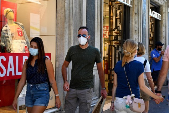 Des personnes portant un masque facial marchent le long de la principale rue commerçante Via del Corso le 20 août 2020 à Rome lors de l'infection COVID-19, causée par le nouveau coronavirus.  - L'Italie a enregistré son plus grand nombre d'infections à coronavirus depuis le 23 mai, avec 845 nouveaux cas signalés le dernier jour, ont déclaré des responsables du ministère de la Santé le 20 août. L'Italie est sortie en mai d'un grave verrouillage après être devenue l'un des premiers pays européens à signaler des cas de COVID-19.  (Photo par Vincenzo PINTO / AFP) (Photo par VINCENZO PINTO / AFP via Getty Images)